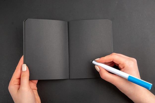 Bovenaanzicht zwarte notitieblok en pen in vrouwelijke handen op zwarte tafel