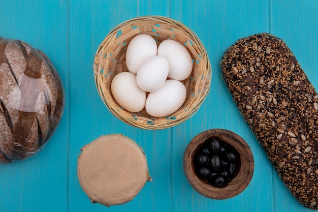 Bovenaanzicht zwarte olijven in een kom met kippeneieren in een mand en zwart brood op een turkooizen achtergrond
