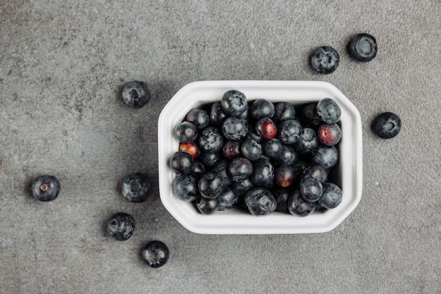 Bovenaanzicht zwarte olijven in vierkante kom op grijze achtergrond. horizontaal