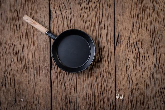 Bovenaanzicht zwarte pan op hout achtergrond