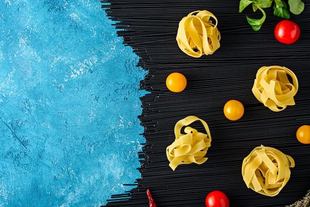 Bovenaanzicht zwarte pasta met inktvis inkt met fettuccine, tomaten en chilipepers op de turquoise keukentafel met kopie ruimte, keuken achtergrond concept