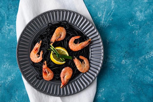Bovenaanzicht zwarte pasta met inktvis inkt met garnalen en schijfjes citroen in grijze plaat op blauwe achtergrond met witte theedoek met kopie ruimte