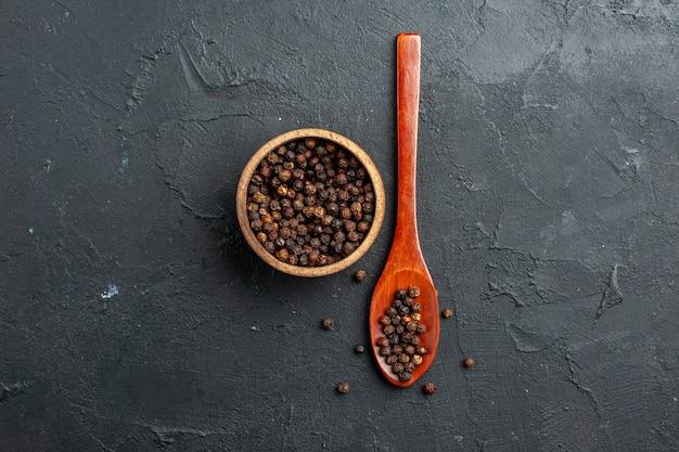 Bovenaanzicht zwarte peper kom houten lepel op donkere oppervlak kopie plaats