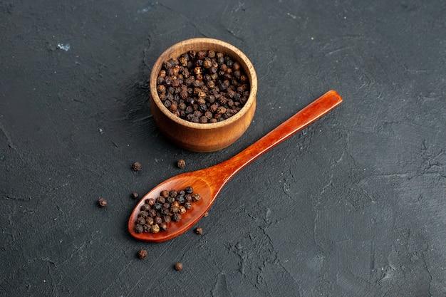 Bovenaanzicht zwarte peper kom houten lepel op zwarte ondergrond