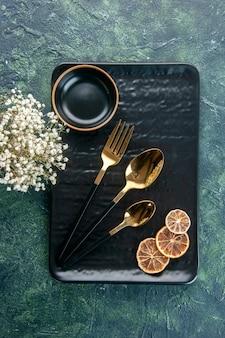 Bovenaanzicht zwarte plaat met gouden bestek op donker oppervlak bestek kleur maaltijd zilver restaurant eten dienblad service diner
