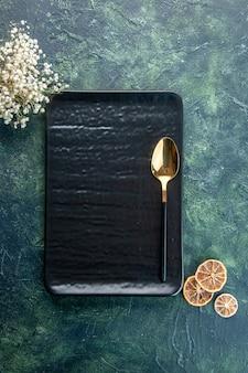 Bovenaanzicht zwarte plaat met gouden lepel op donkerblauwe ondergrond eten restaurant bestek maaltijd service kleur