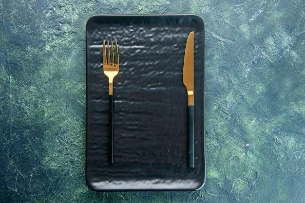 Bovenaanzicht zwarte plaat met gouden vork en mes op donkere achtergrond kleur diner bestek maaltijd restaurant utencil food