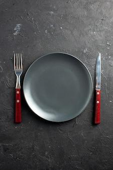 Bovenaanzicht zwarte plaat vork en mes op zwarte ondergrond
