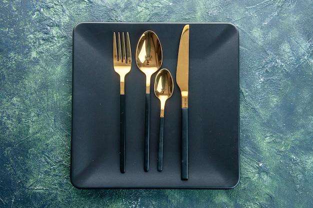 Bovenaanzicht zwarte platen met gouden lepels mes en vork op donkere achtergrond kleur eten diner keuken restaurant bestek