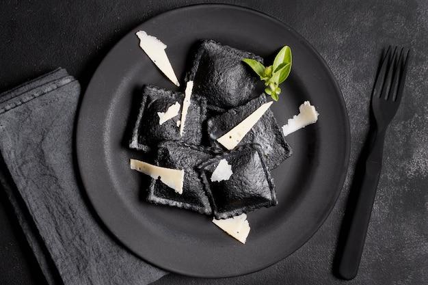 Bovenaanzicht zwarte ravioli en plakjes kaas