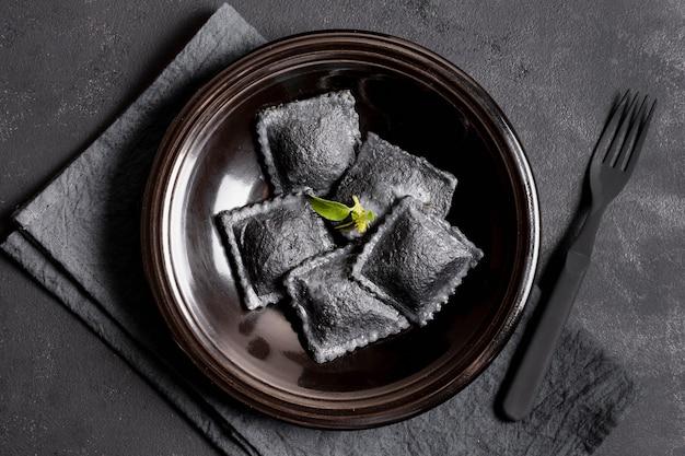 Bovenaanzicht zwarte ravioli op plaat met vork