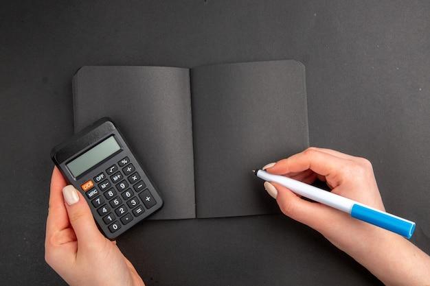 Bovenaanzicht zwarte rekenmachine en pen in vrouwelijke notitieblok op zwarte tafel