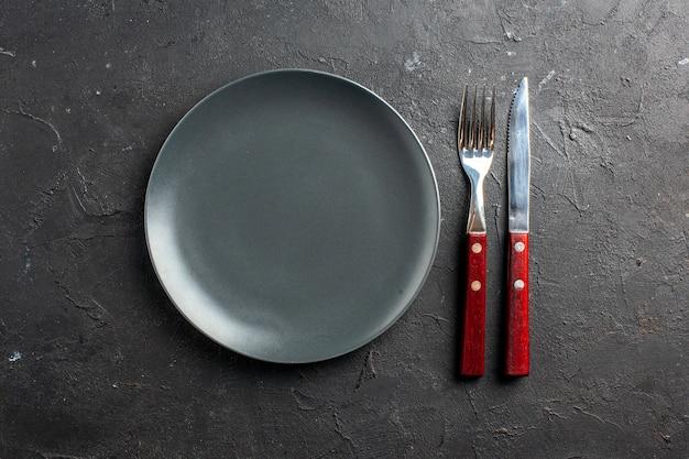 Bovenaanzicht zwarte ronde plaat een mes en vork op zwarte ondergrond