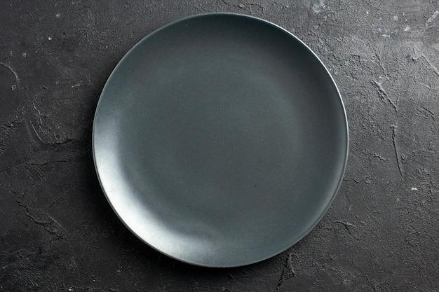 Bovenaanzicht zwarte salade plaat op zwarte ondergrond