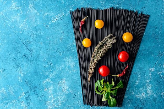 Bovenaanzicht zwarte spaghetti met inktvisinkt op blauwe achtergrond met gele en rode tomaten, tijm en chilipepers met kopie ruimte