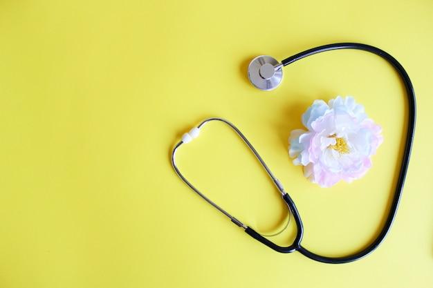Bovenaanzicht zwarte stethoscoop op geel. voor check hart of gezondheidscontrole. copyspace