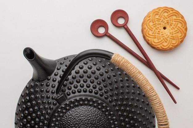 Bovenaanzicht zwarte theepot met zelfgemaakte koekje