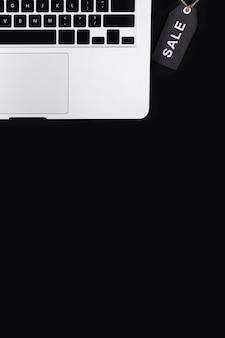 Bovenaanzicht zwarte verkoop tag in de buurt van laptop