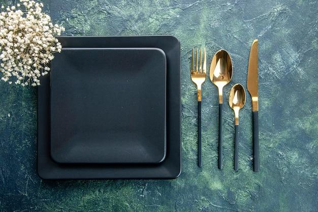 Bovenaanzicht zwarte vierkante borden met gouden vork lepels en mes op donkerblauwe achtergrond diner keuken restaurant eten bestek kleur