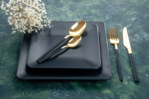 Bovenaanzicht zwarte vierkante borden met gouden vork lepels en mes op donkere ondergrond kleur eten bestek diner restaurant