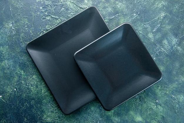 Bovenaanzicht zwarte vierkante borden op donkere achtergrond diner restaurant eten bestek kleur keuken maaltijd utencil duisternis