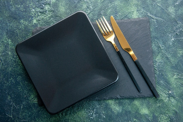 Bovenaanzicht zwarte vierkante plaat met gouden vork en mes op donkere achtergrond kleur eten restaurant bestek diner keuken