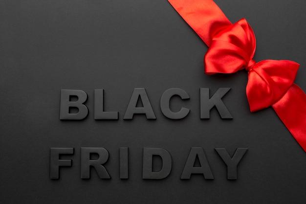Bovenaanzicht zwarte vrijdag brieven samenstelling met rood lint
