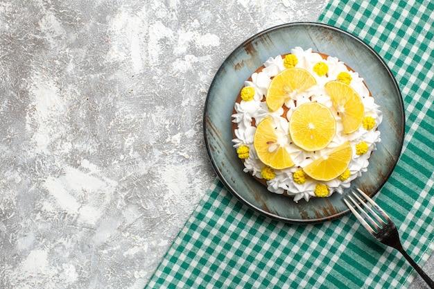 Bovenaanzichtcake met banketbakkersroom en citroen op ronde plaatvork op groen wit geruit tafelkleed