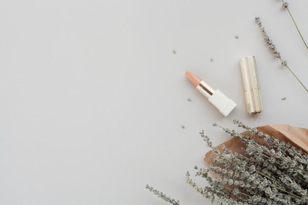Bovenaanzichtdecoratie met bruine lippenstift en plant