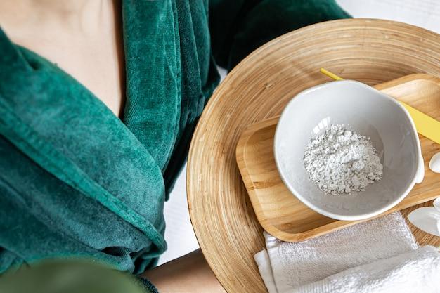 Bovenaanzichtplaat met gezichtsmasker van klei in vrouwelijke handen