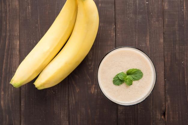 Bovenkant geschotene banaan smoothie op houten lijst