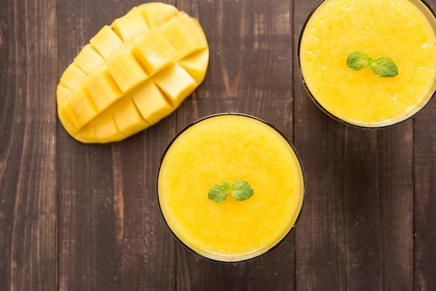 Bovenkant geschotene mango smoothie op houten lijst