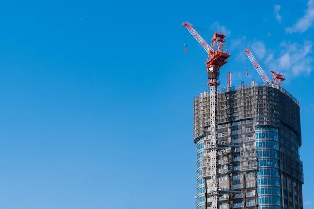 Bovenkant van bouwwerf met kranen op blauwe hemelachtergrond met exemplaarruimte