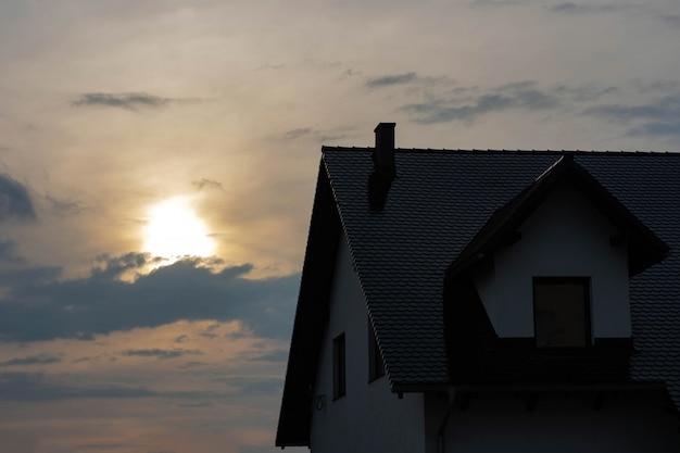 Bovenkant van het huis met een dak en een zolder bij zonsondergang.