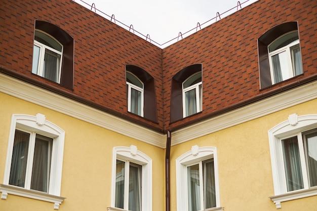 Bovenkant van twee huisgevels een wit hemel rood dak