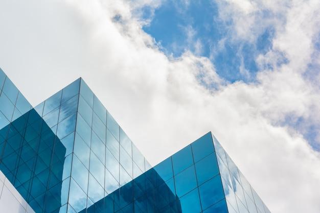 Bovenkant van wolkenkrabberzaken die op blauwe hemel voortbouwen