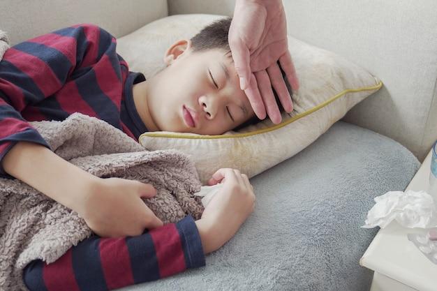 Bovenliggende hand controleren op zieke preteen rusten op de bank met medicatie thuis