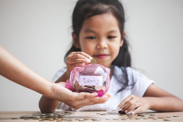 Bovenliggende hand met spaarvarken en schattig aziatisch kind meisje geld steken in spaarvarken