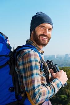 Bovenop. knappe jonge man die rugzak draagt en met een glimlach door de schouders naar de camera kijkt terwijl hij in de natuur staat en een verrekijker vasthoudt