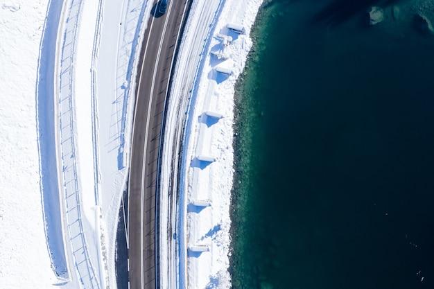 Bovenopname van een asfaltweg naast een meer, vastgelegd in de winter
