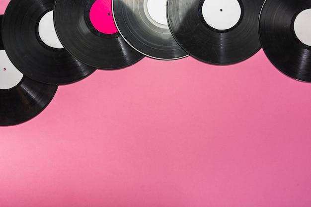 Bovenrand gemaakt met vinylplaten op roze achtergrond