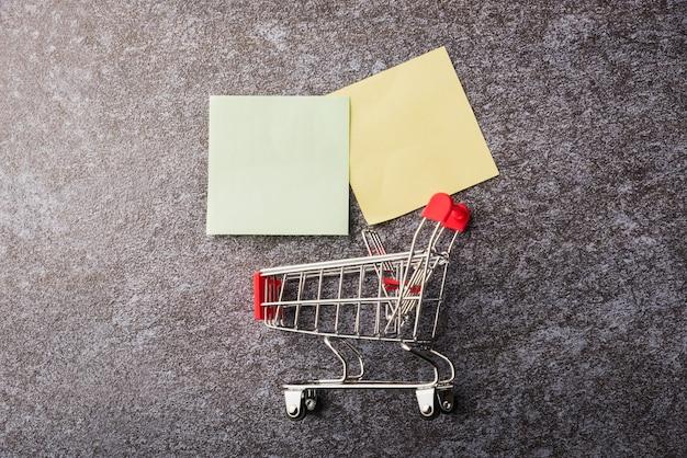 Bovenstaande blanco papier notitie lijst geel en groen met de winkelwagen