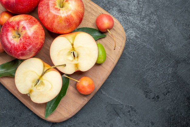 Bovenste close-up appels de snijplank van kersen appels citrusvruchten