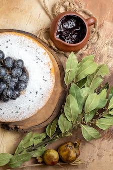 Bovenste close-up bekijken een cake een cake met druiven op het bord chocoladesaus bladeren