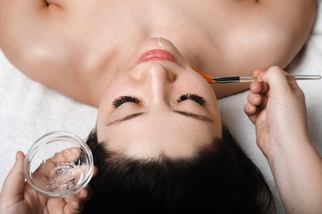 Bovenste close-up portret van een knappe jonge blanke vrouw leunend op een spa-bed met gesloten ogen terwijl een transparant gezichtsmasker door schoonheidsspecialist doet.