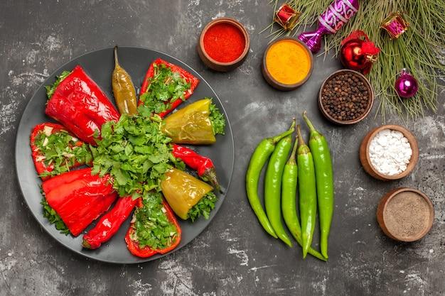 Bovenste close-up schotel pepers met kruiden hete pepers specerijen kerstboom speelgoed
