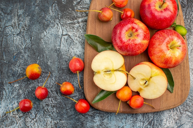 Bovenste close-up weergave appels rode appels kersen op de snijplank