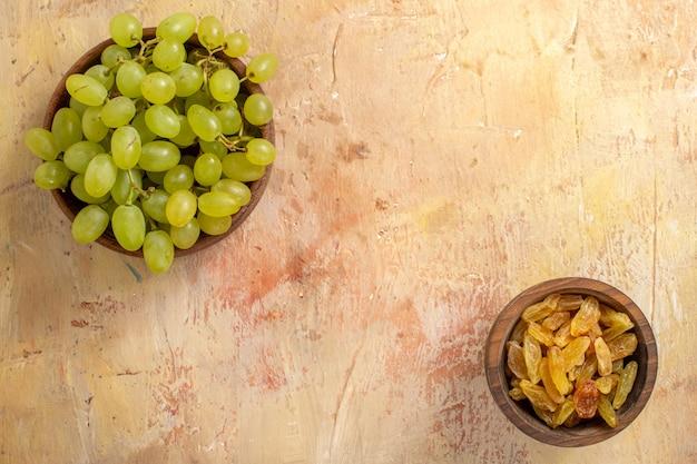Bovenste close-up weergave druiven kommen rozijnen en groene druiven op tafel