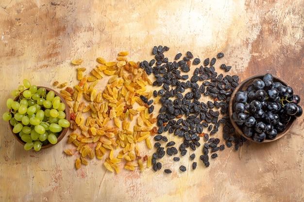 Bovenste close-up weergave druiven zwarte en groene druiven in kommen groene en zwarte rozijnen op tafel