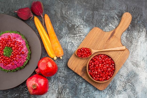Bovenste close-up weergave kerst schotel schotel granaatappels groenten de snij plank met granaat appel